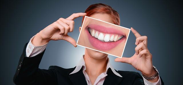 imagen de una mujer con una fotografía de una dentadura perfecta gracias a los implantes dentales