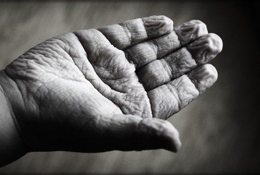 mano arrugada de un niño simula los efectos del envejecimiento en las personas