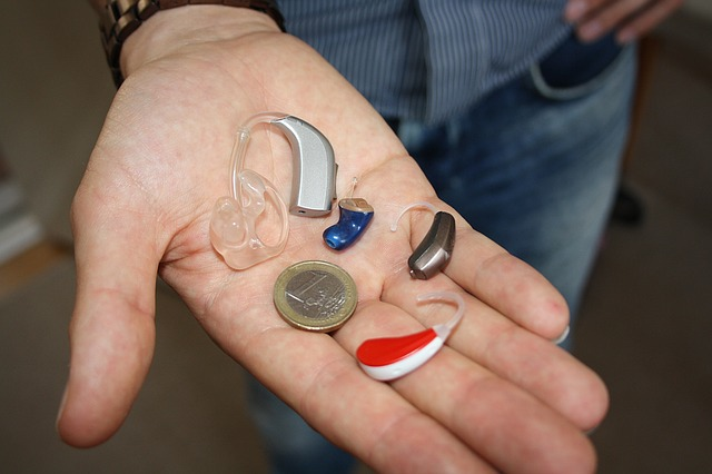 mano mostrando varios dispositivos auditivos