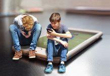 dos adolescentes usando sus dispositivos móviles. De fondo un smartphone