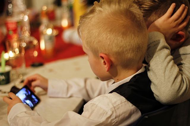 Un niño pequeños haciendo uso de un smartphone.