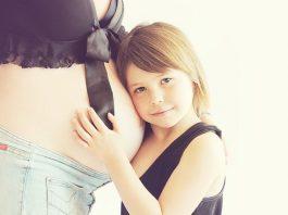 niña apoyando la cabeza sobre la barriga de embarazada de su madre