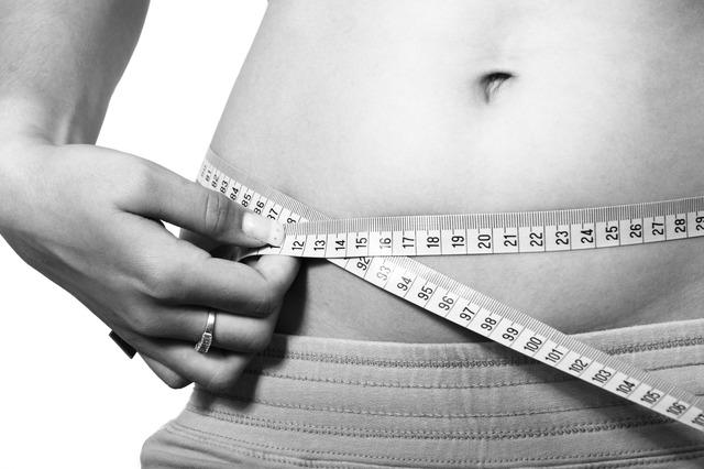 imagen mostrando a una mujer midiéndose la cintura con una cinta métrica. Cuidado con las dietas peligrosas
