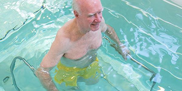 anciano realizando una terapia acuática para la recuperación de una fractura de cadera.