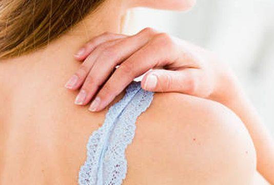 mujer tocándose la espalda. ¿Qué relación existe entre la dieta y la psoriasis?