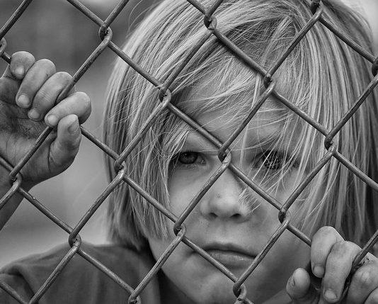niño detrás de una verja. ¿Aumentan los trastornos mentales en esta generación?